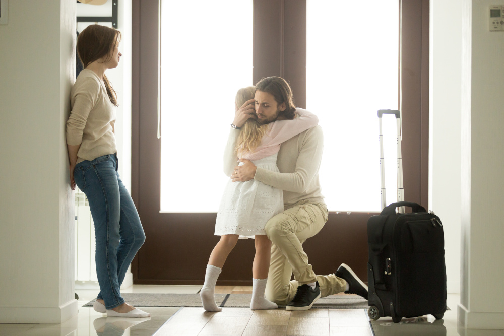co-parenting; man hugging children with luggage