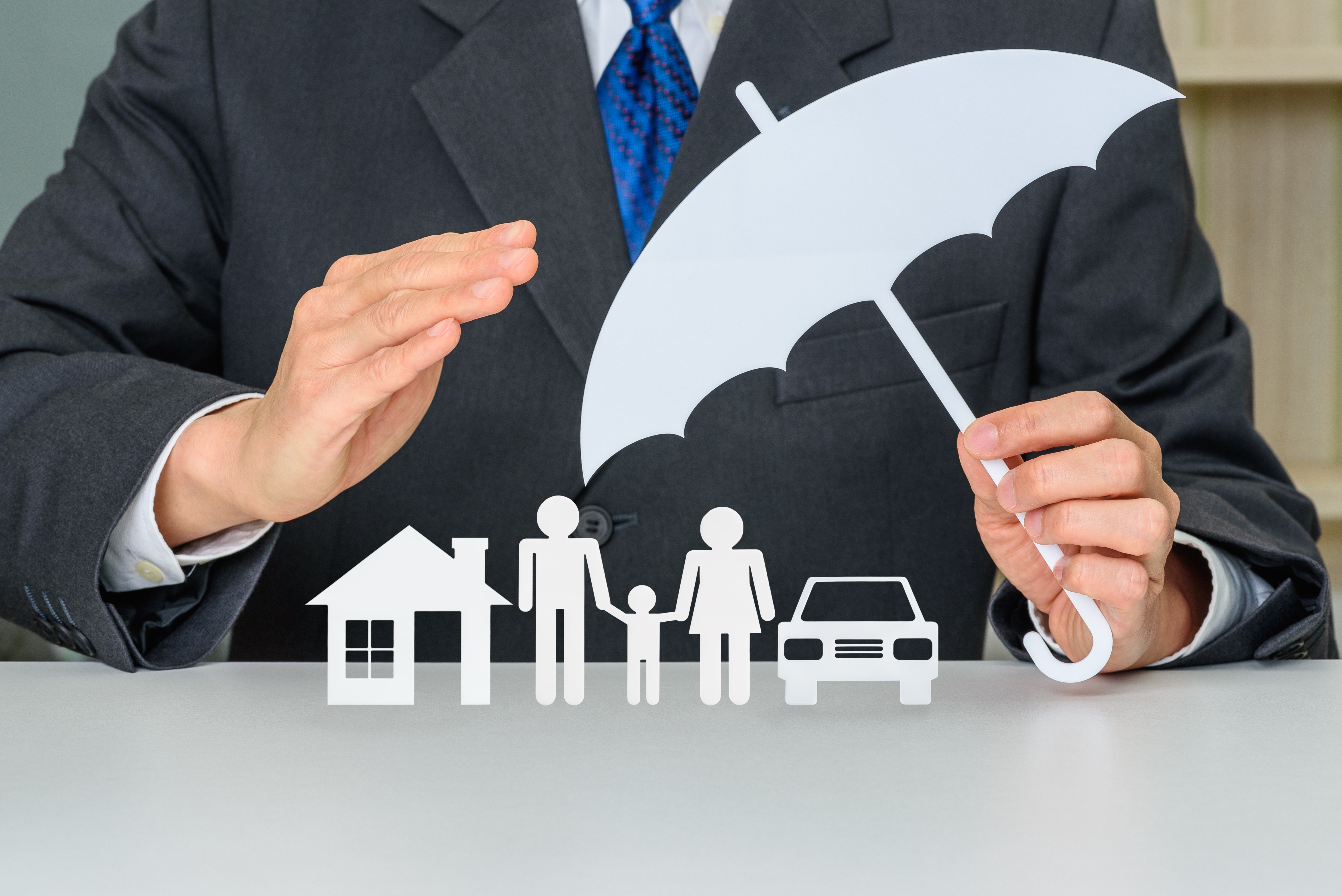 asset protection, man protecting assets with paper cutouts