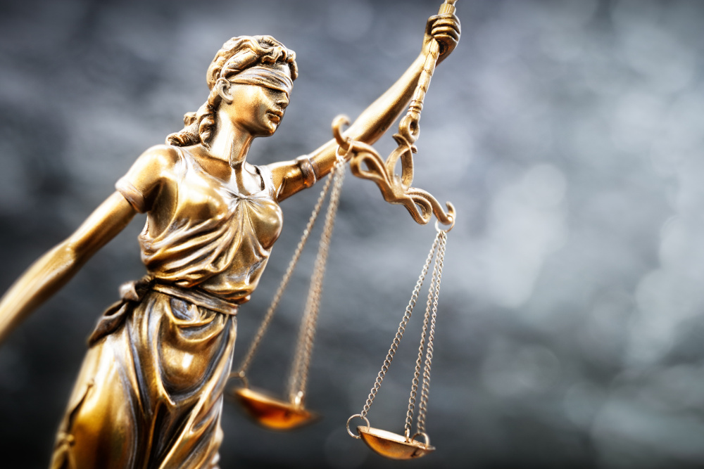 justice statue with scales and blue background